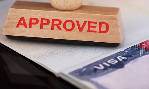 Close-up Photo Of Approved Stamp On Visa
