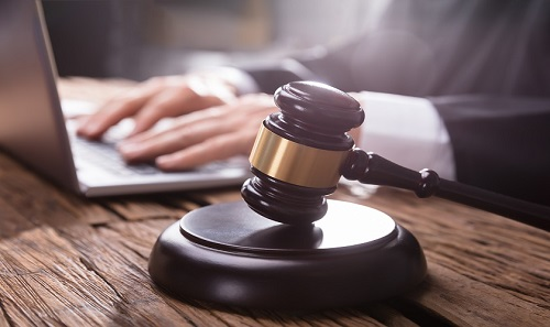 Close-up Of A Gavel On Wooden Desk In Front Of Judge Working On Laptop